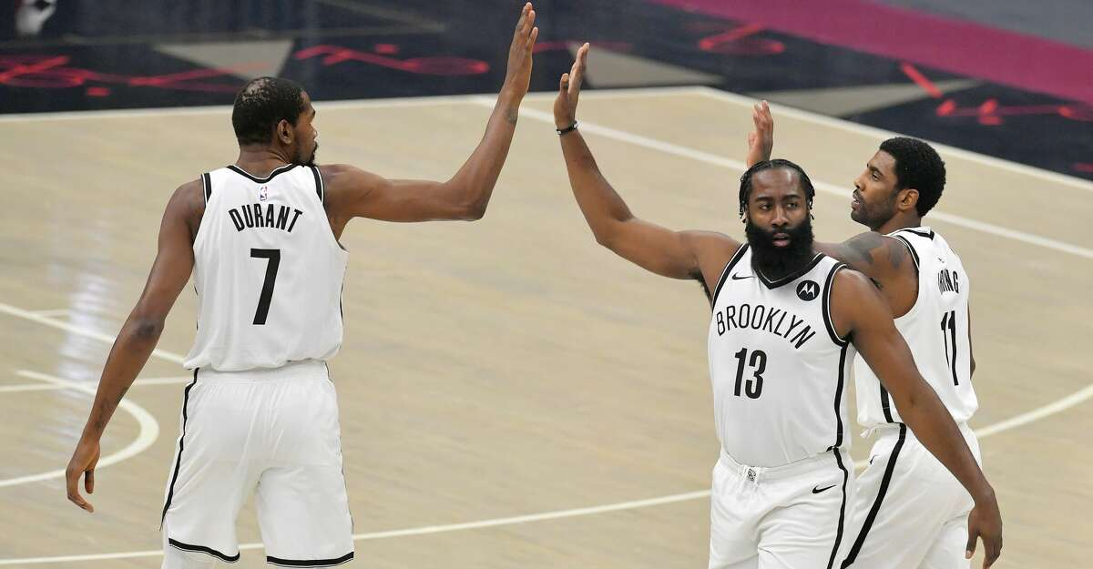 The Brooklyn Nets' Kevin Durant (7), James Harden (13) and Kyrie Irving (11) celebrate action against the Cleveland Cavaliers at Rocket Mortgage Fieldhouse in Cleveland on January 20, 2021. (Jason Miller/Getty Images/TNS)