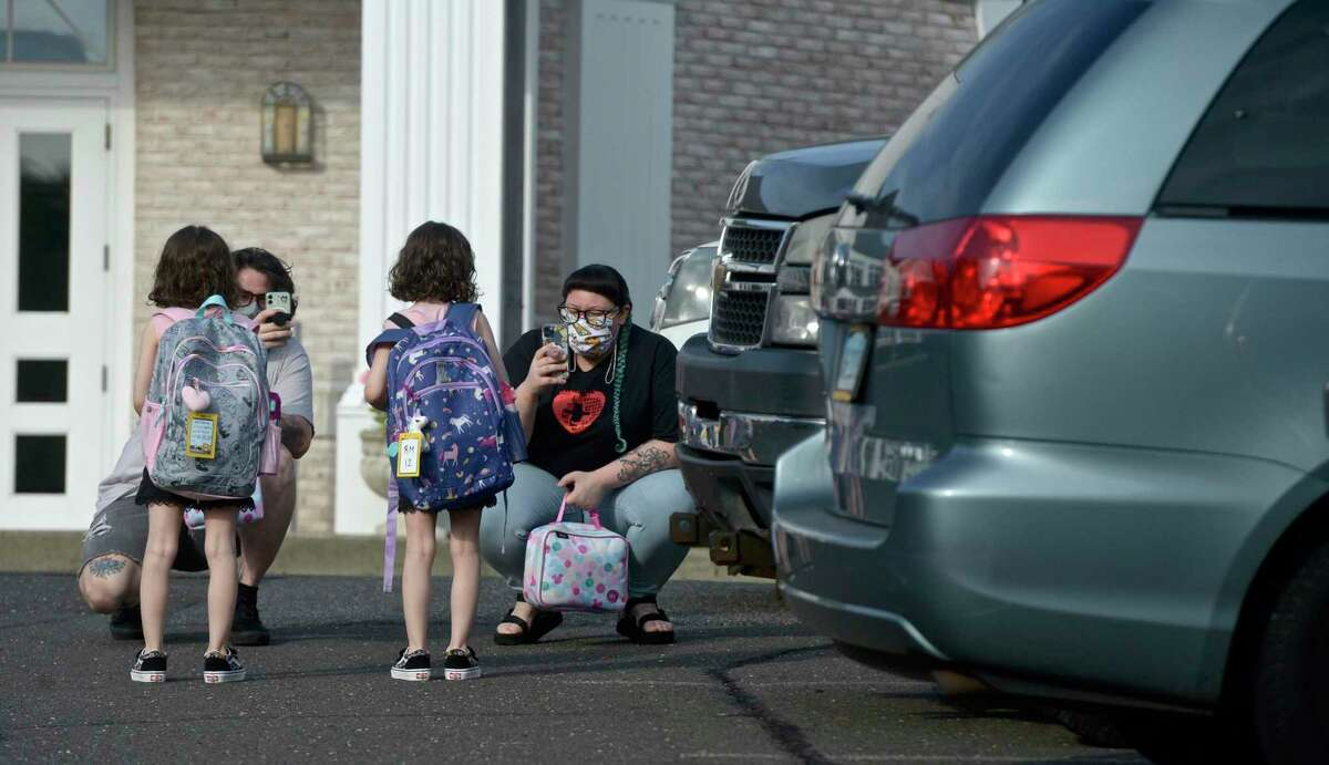 Ian Copland, left, and Megan Tucker, of Danbury, take photographs while dropping off their twin daughters Lilith, left, and Lydia Copland for the first day of kindergarten at the Danbury Primary Center in Brookfield. Monday, August 30, 2021, Brookfield, Conn.