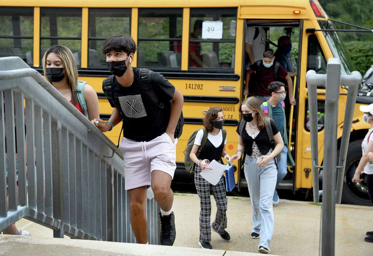 Students, all wearing masks, arrive for the first day of school at Fairfield Ludlowe High School in Fairfield on Aug. 30, 2021.