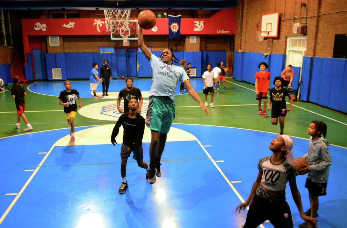 Kids play basketball at the Orcutt Boys & Girls Club on Park Street in Bridgeport, Conn., on Jan. 2, 2020. Christina Skrieh, of Orange, who takes her son to the club for basketball, spearheaded a daily meal train to feed the kids who spend time there after school.