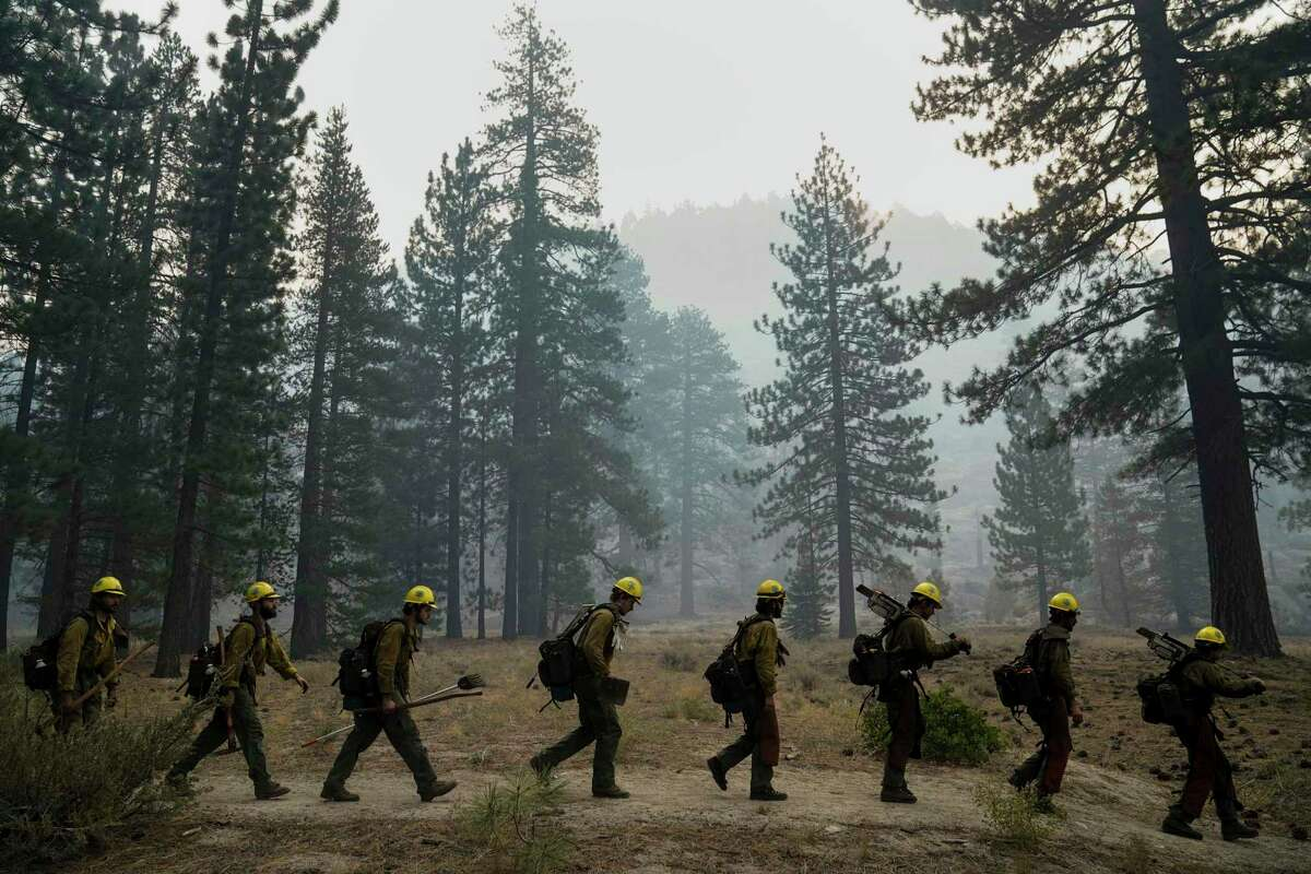 A hotshot crew from Tahoe Hotshots, working the Caldor Fire, hikes along a trail in Meyers (El Dorado County) on Friday, Sept. 3.