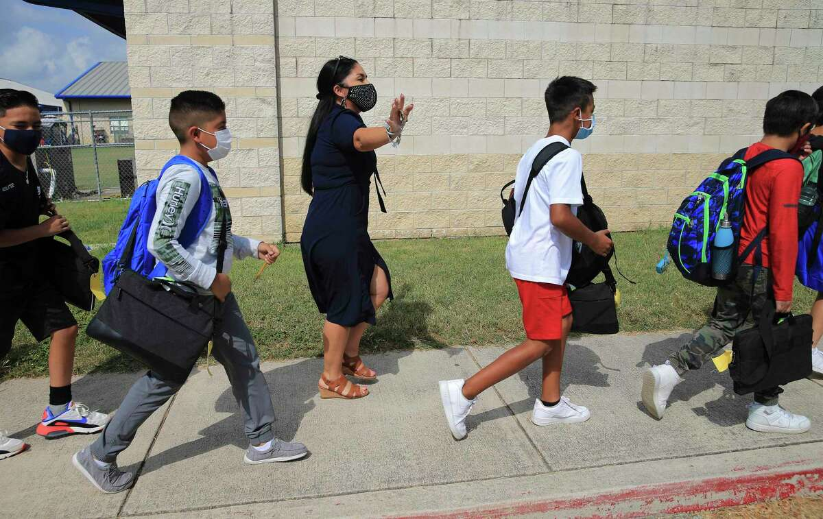 Savannah Heights Intermediate principal Cynthia Gamez (center) walks along with fifth-grade students Thursday on their way to the cafeteria for lunch. Somerset ISD is confident it can limit coronavirus exposure at its campuses. Some districts have developed contingency plans in case large numbers of students and staff have to quarantine.