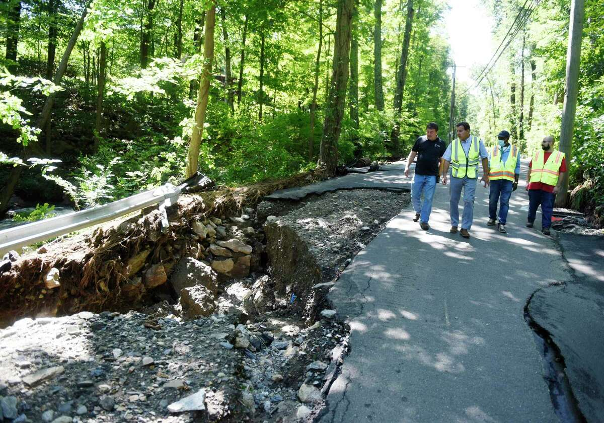 Workers view damage to a stretch of Farms Road in Stamford, Conn., after the remnants of Hurricane Ida dumped several inches of rain on Sept. 1, 2021, causing flooding in some part of the city.