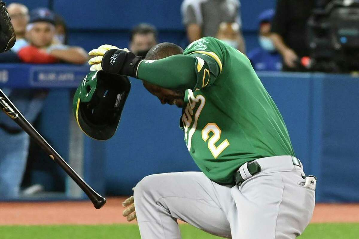 Oakland Athletics' Starling Marte reacts after getting hit on the helmet by a pitch thrown by Toronto Blue Jays' Alek Manoah during the fifth inning of a baseball game Friday, Sept. 3, 2021, in Toronto. (Jon Blacker/The Canadian Press via AP