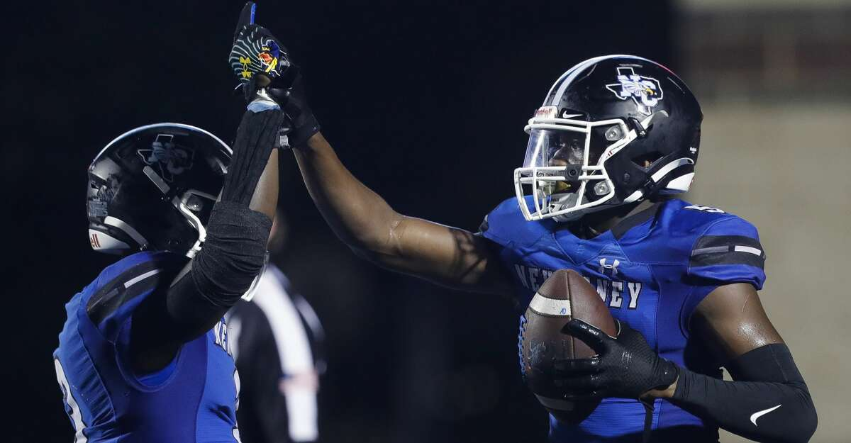 New Caney wide receiver Cameron Thomas (5) gets a high-five from running back Kedrick Reescano (3) after scoring a 6-yard touchdown during the fourth quarter of a high school football game at Randall Reed Stadium, Friday, Sept. 3, 2021, in New Caney.
