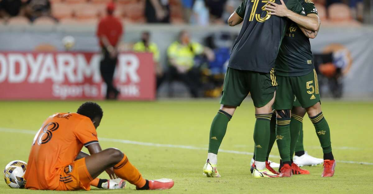 Houston Dynamo defender Teenage Hadebe, left, reacts as Portland Timbers' Dario Zuparic (13) and Claudio Bravo (5) hug as the clock runs out on the Timbers' win in an MLS soccer match Friday, Sept. 3, 2021, in Houston. (AP Photo/Michael Wyke)