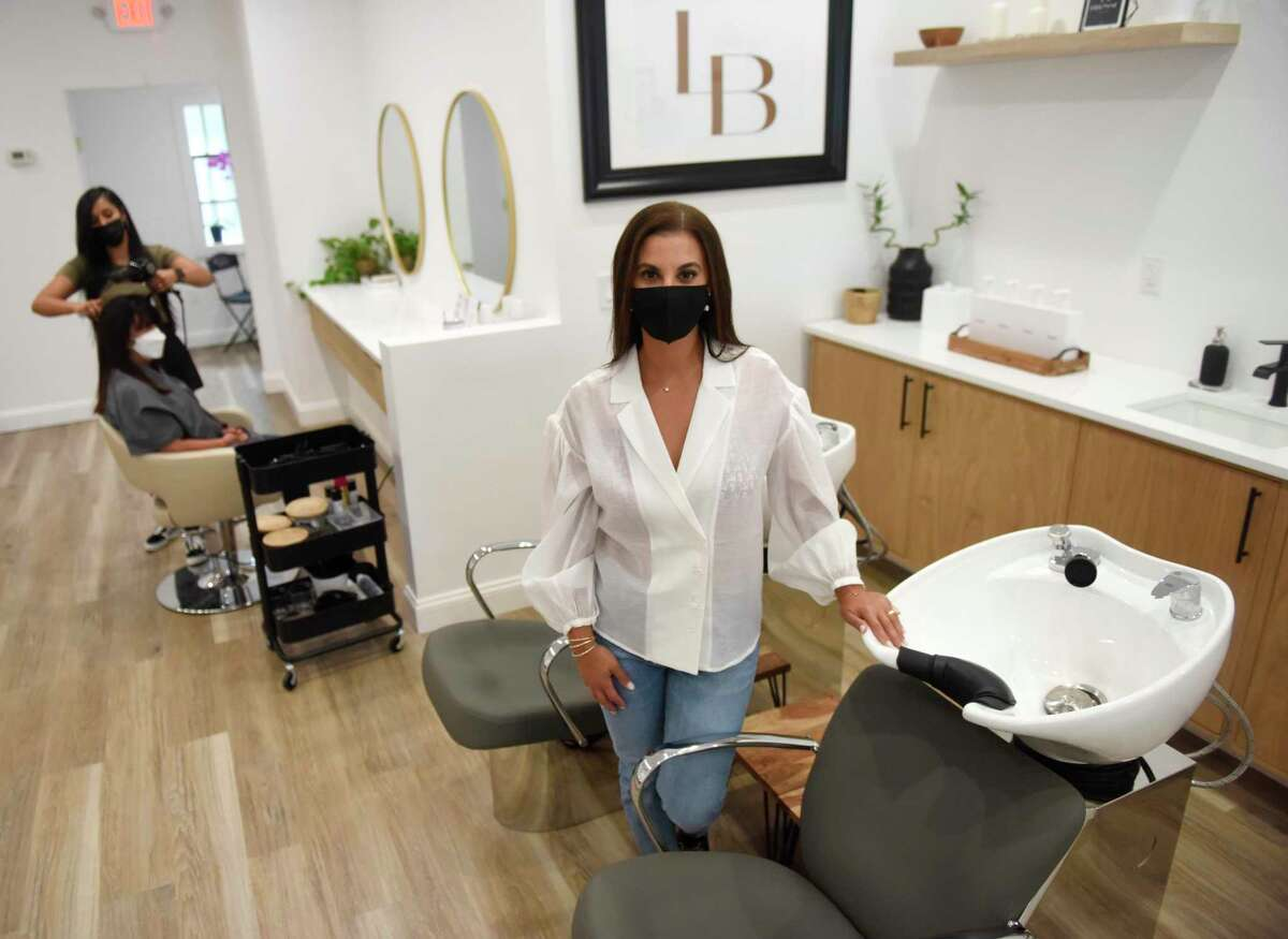 Owner Stephanie Leone-Kim poses at La Brosse Dry Bar in the Cos Cob section of Greenwich, Conn. Tuesday, Aug. 31, 2021. The salon located in Mill Pond Shopping Center opened over the summer and offers blow dry services, keratin treatment, and bridal hair styling.