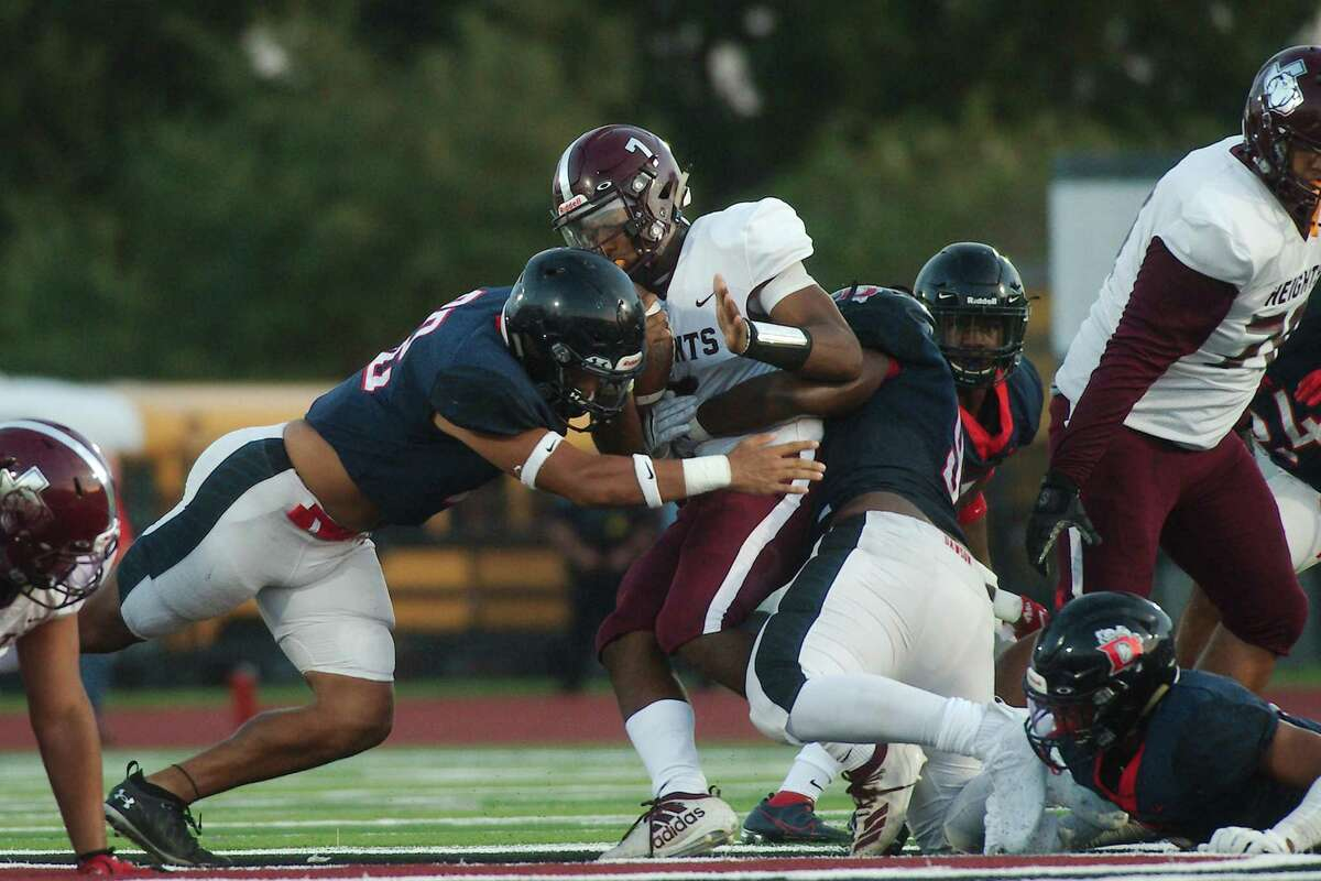 Houston Heights' Jalen Morrison (7) is hit hard by Dawson's Jackson Cody (32) and Timothy Granderson (97) Friday at Pearland Stadium.
