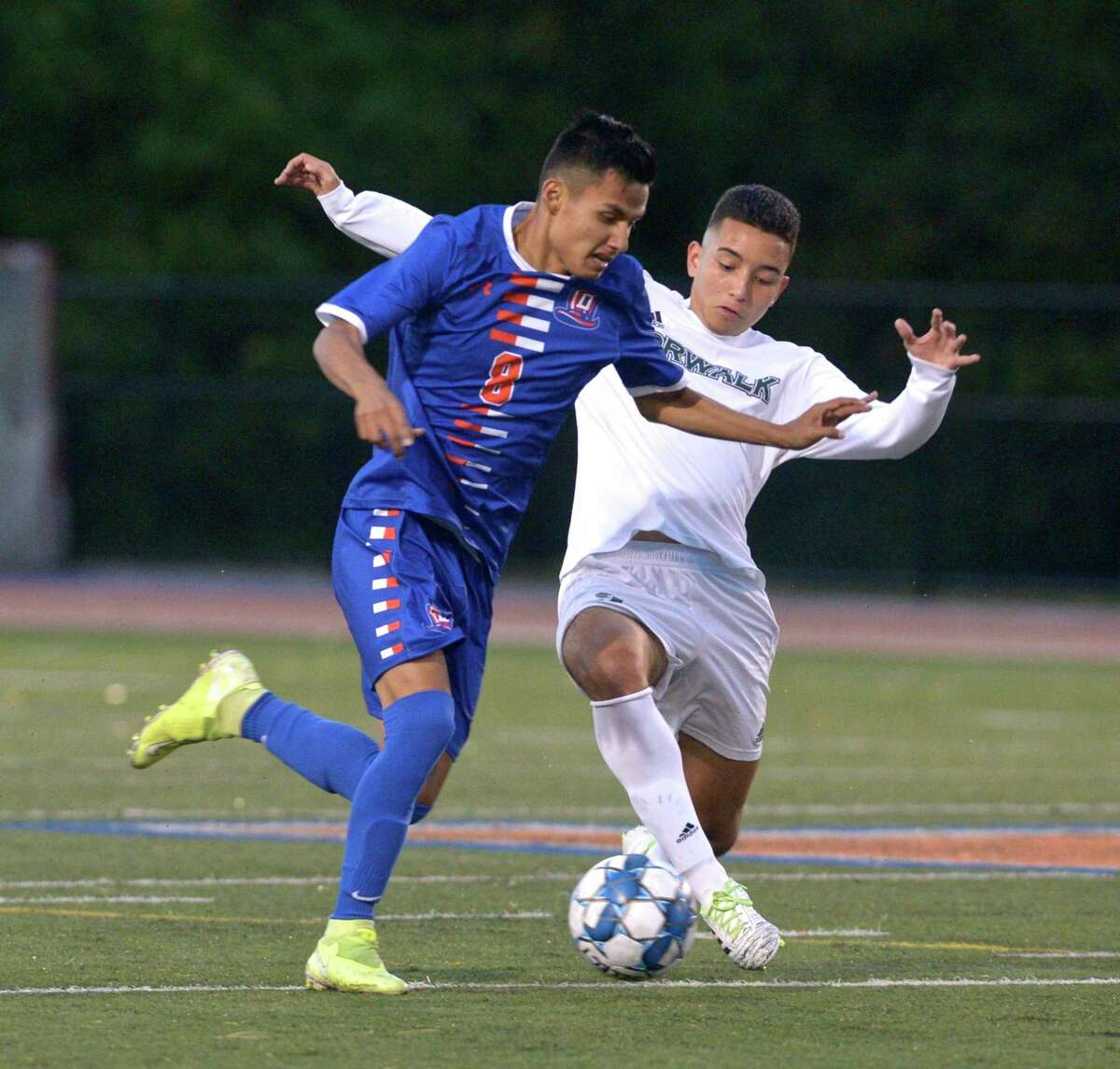 Danbury's Jeremy Garcia (8) and Norwalk's Mateo Cano (9) battle for the ball in the boys soccer game between Norwalk and Danbury high schools. Wednesday night, October 7, 2020, at Danbury High School, Danbury, Conn.