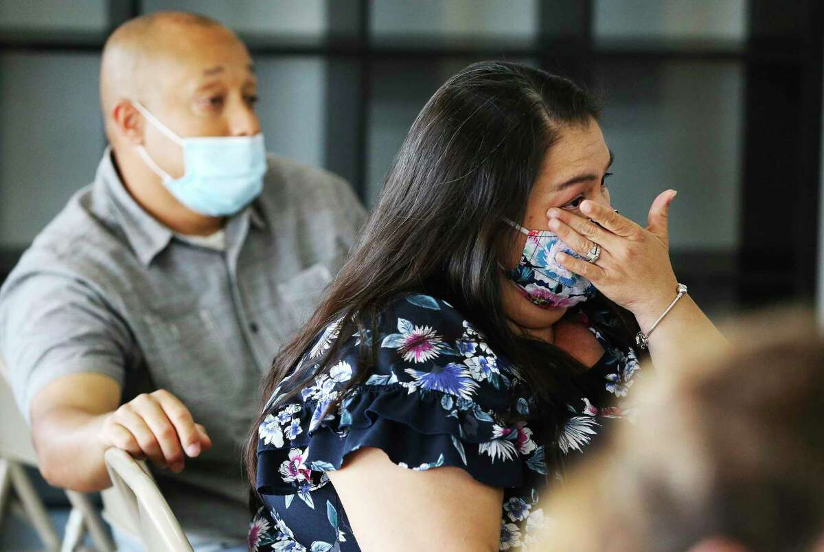 San Antonio resident Brenda Colón, 42, a COVID-19 survivor, wipes tears from her eyes as she and her husband, Saul, watch their son, Cristian, receive his Black Belt at KOA Kenpo Karate on Friday. She was able to attend after surviving a near deadly bout of COVID-19 last month with the help of an antibodies infusion. The treatment improved her worsening condition and Colón began to recover within 24 hours.