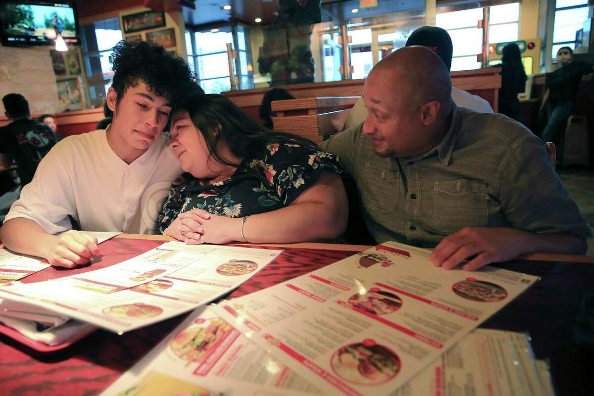 San Antonio resident Brenda Colón, 42, a COVID-19 survivor, shares a moment with her son, Cristian, as she and her husband, Saul, enjoyed a celebratory meal after the teen received his Black Belt at KOA Kenpo Karate on Friday. She survived a near deadly bout of COVID-19 in August with the help of an antibodies infusion manufactured by Regeneron Pharmaceuticals.