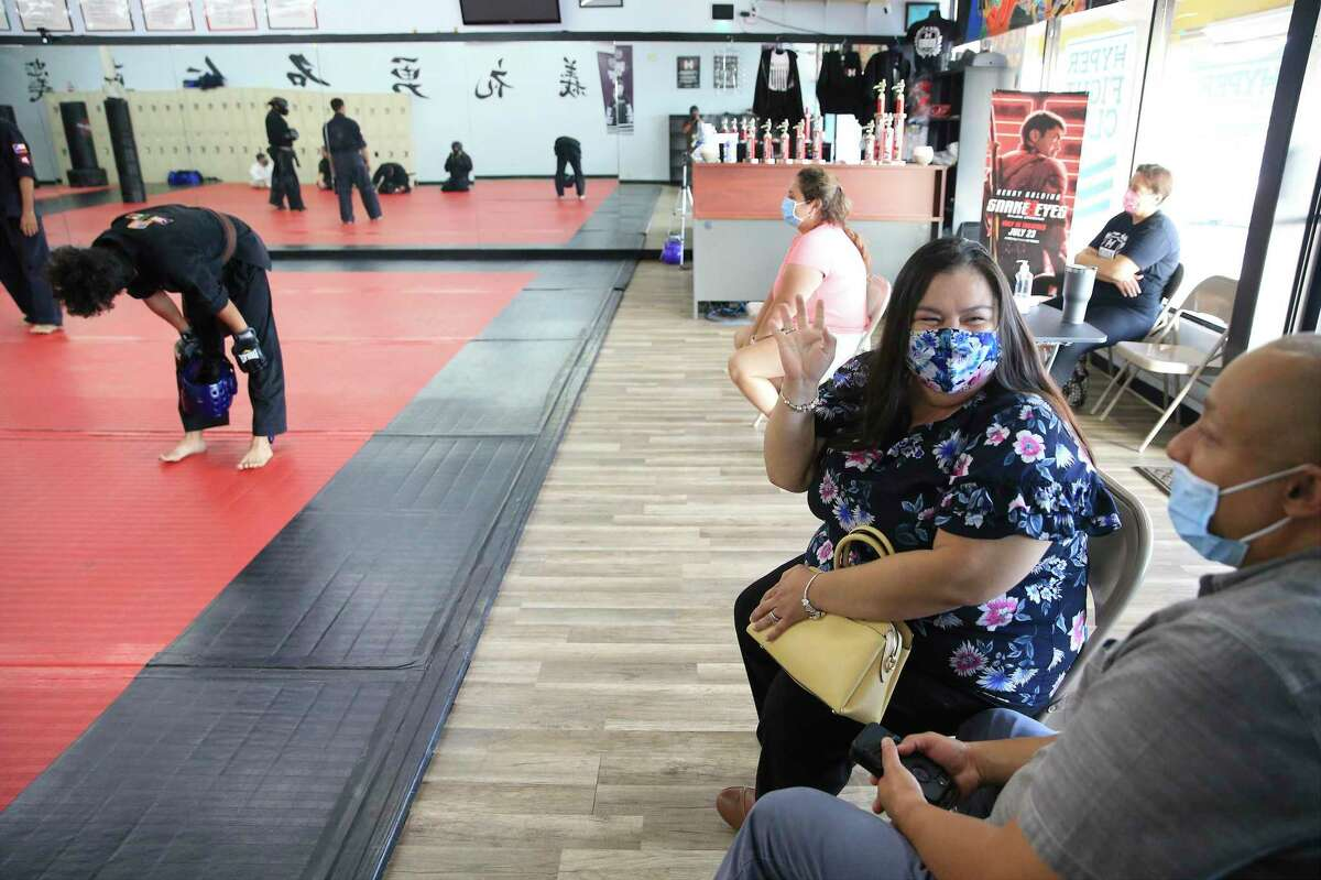 Brenda Colón, 42, a COVID-19 survivor who lives in San Antonio, turned to her husband, Saul, after they watched their son, Cristian, receive his Black Belt at KOA Kenpo Karate on Friday. Colón was able to witness her son's achievement after surviving a near deadly bout of COVID-19 last month with the help of an antibodies infusion. The treatment quickly reversed her worsening condition and Colón began to recover within 24 hours.