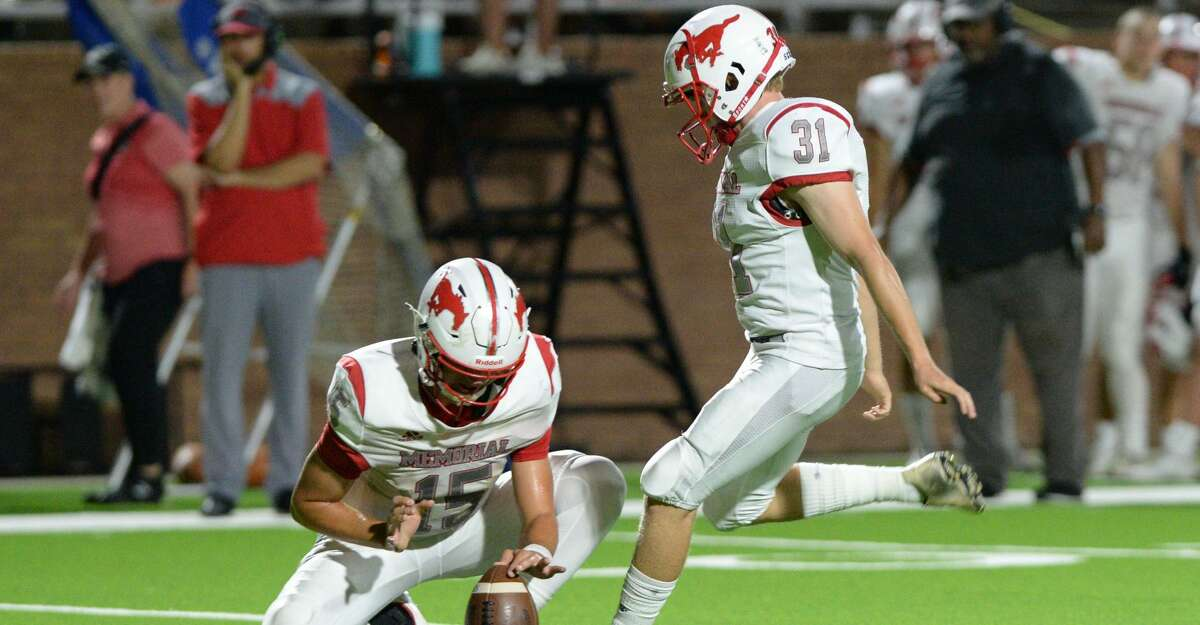 Chase Goodwin (15) of Memorial holds the ball as Carter Kenne (31) kicks a field goal during the third quarter of a non-District football game between the Seven Lakes Spartans and the Memorial Mustangs on Friday, August 27, 2021 at Rhodes Stadium, Katy, TX.