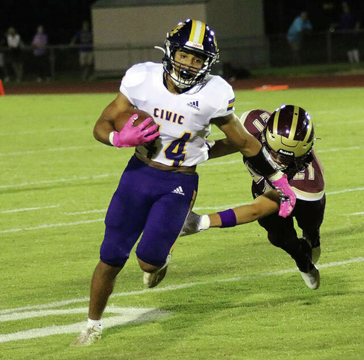 CM's Miguel Gonzalez (left) turns the corner while eluding EA-WR's Kiyu Stilts in the third quarter Friday night at Memorial Stadium in Wood River.