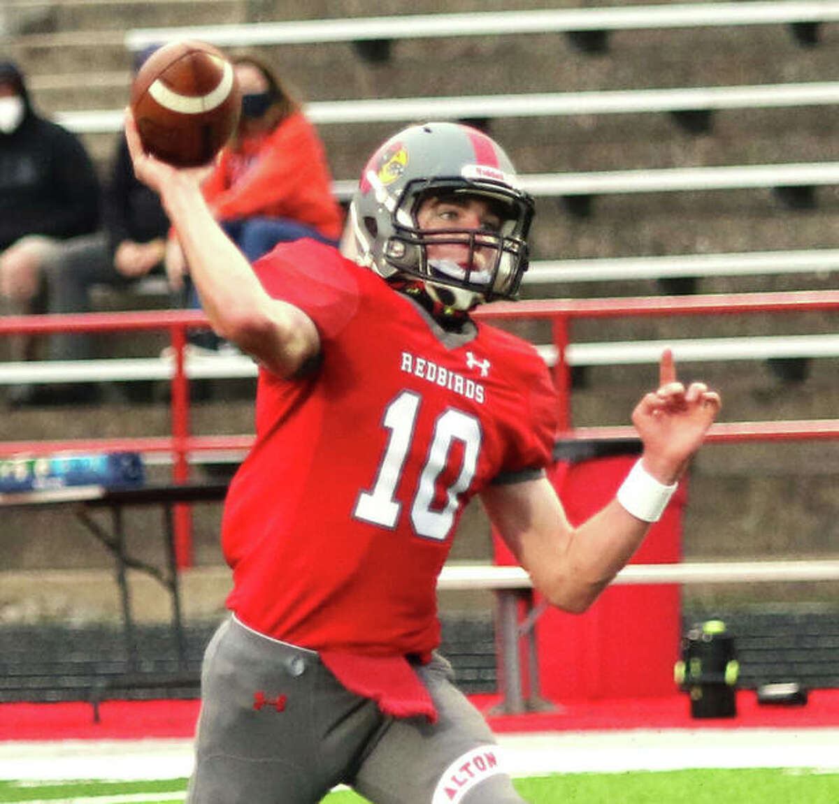 Alton quarterback Graham McAfoos threw a 20-yard touchdown pass to Jaylen Telford, but the Redbirds dropped a 27-20 decision to Quincy Friday night at Public School Stadium. McAfoos is shown in action against Champaign Central during the spring season