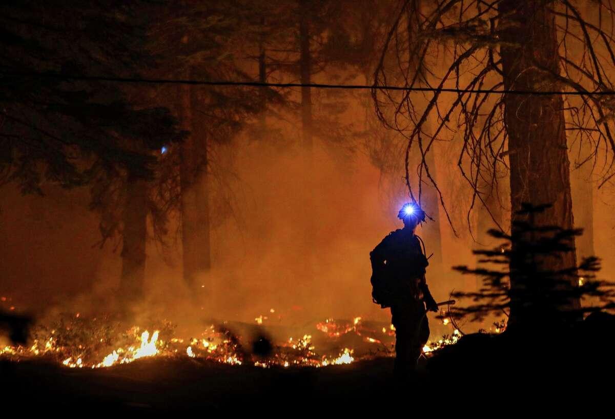 A firefighter monitors flames near a home outside Strawberry (El Dorado County) last Sunday.