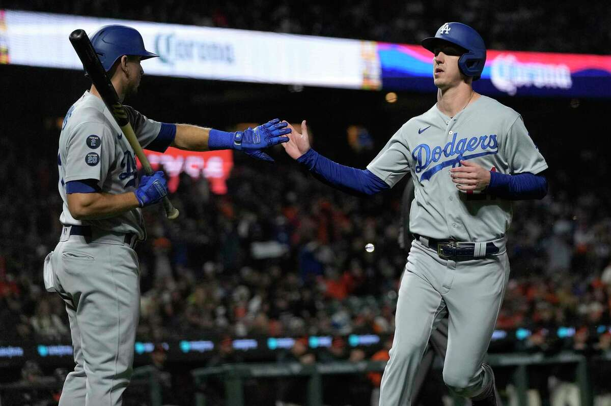 Los Angeles Dodgers' Walker Buehler, right, is congratulated by Austin Barnes after scoring on a sacrifice fly by Trea Turner against the San Francisco Giants during the 10th inning of a baseball game Friday, Sept. 3, 2021, in San Francisco. (AP Photo/Tony Avelar)