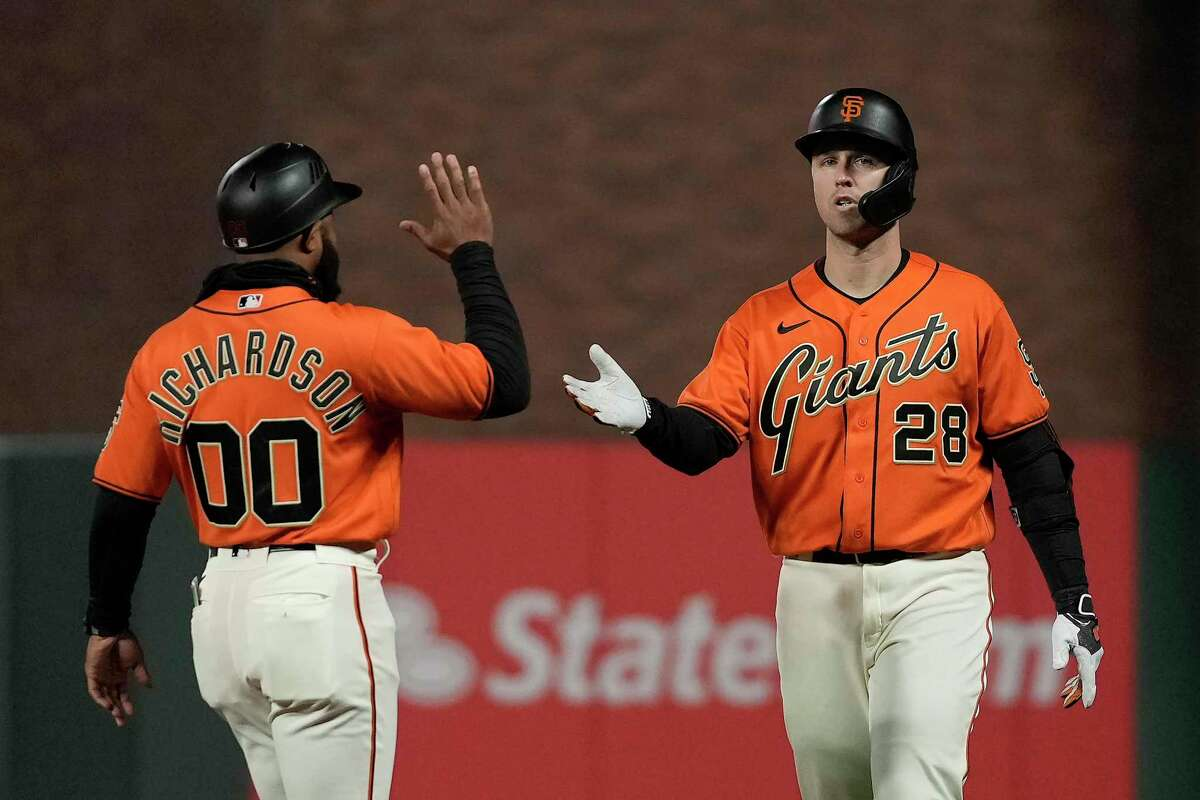 San Francisco Giants' Buster Posey (28) is congratulated by first base coach Antoan Richardson (00) after beating the throw to first base against the Los Angeles Dodgers during the 11th inning of a baseball game Friday, Sept. 3, 2021, in San Francisco. The Giants won 3-2. (AP Photo/Tony Avelar)