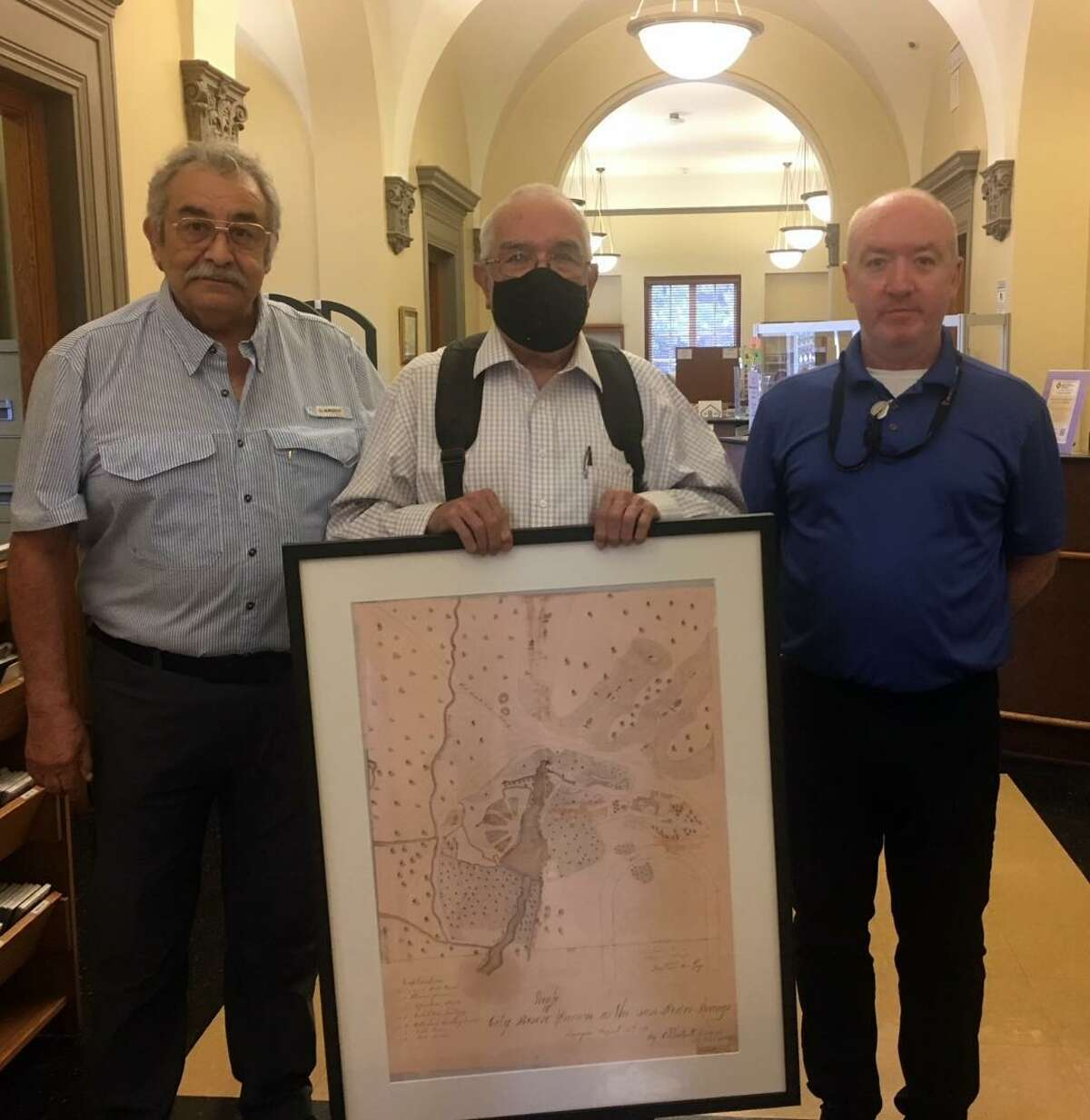 Friends of the San Pedro Springs Park President Hector J. Cardenas, left, and local historian Ed Gaida, center, who gave a recent presentation on the park's history, including the zoo, donate a copy of a rare 1871 map of the park to San Pedro Branch Library Manager Nathaniel Laubner, right. The map will be displayed at the entrance to the library.