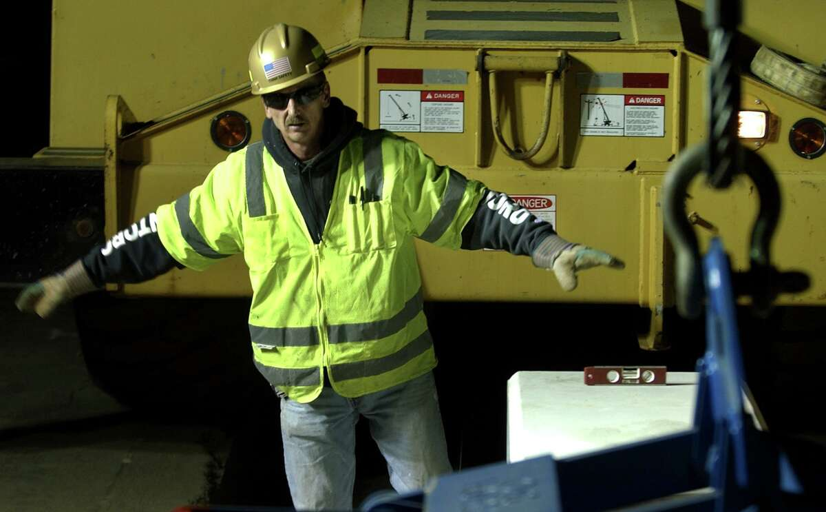 A file photo of an O&G Industries worker positioning a roadway divider in Trumbull, Conn. O&G was among the early adopters of a system created by Triax Technologies to keep tabs of workers on construction job sites. In 2020, the Norwalk startup re-engineered the system to signal if workers violate six feet of distance and keep a log for contact tracing.