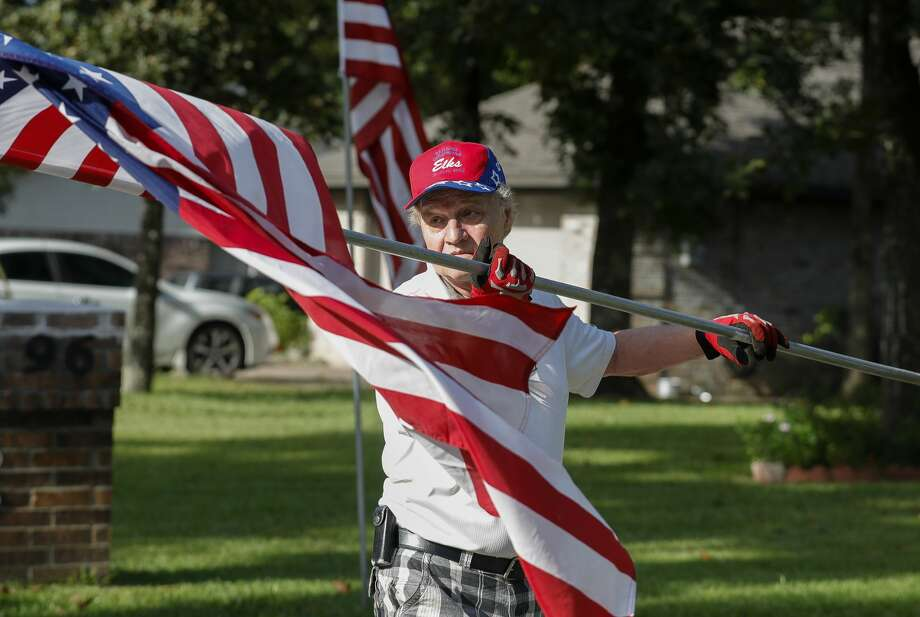 Panorama Lions Club member Bill King unrolls an American flag as he and his wife, Kim, install flags in front of homes for the Labor Day weekend, Saturday, Sept. 4, 2021, in Panorama. The club's program, which places flags outside of people's homes six days a year, raises $20,000 that the club then uses in various charitable community projects. Photo: Jason Fochtman/Staff Photographer / 2021 © Houston Chronicle