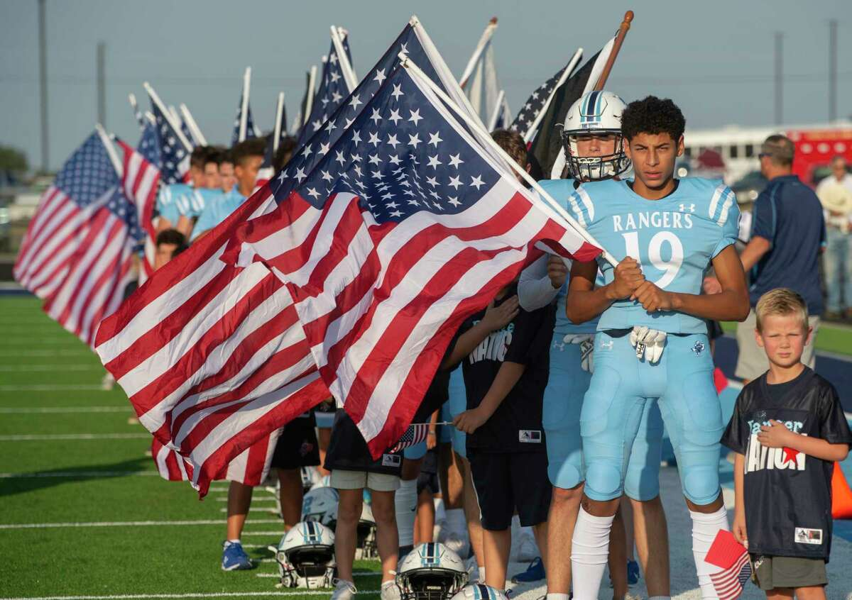Greenwood players hold flags during the National Anthem 09/03/2021 at J.M. King Memorial Stadium as they prepare to play Brownwood. Tim Fischer/Reporter-Telegram