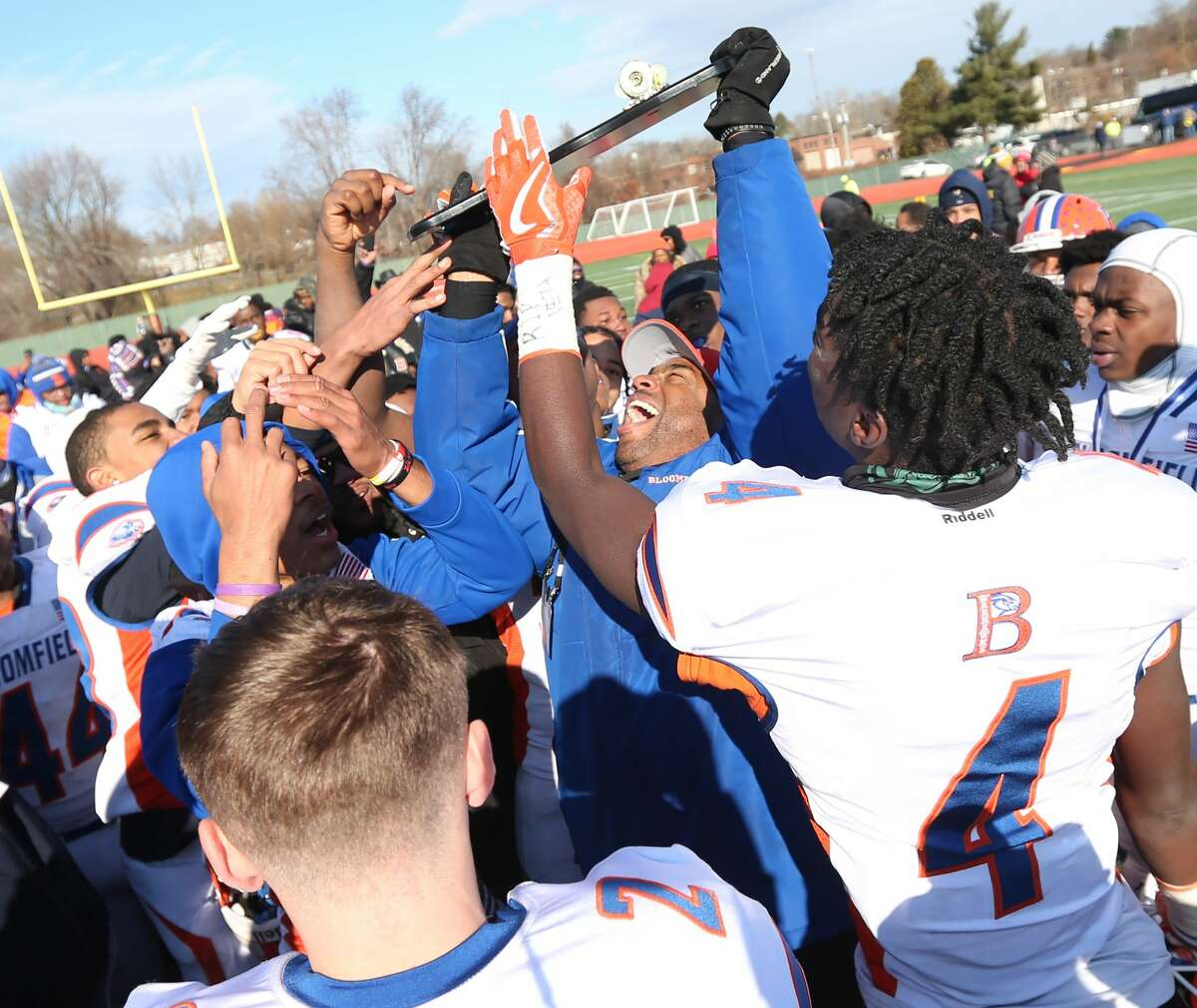 Bloomfield High School football head coach Tylon Outlaw raises the championship plaque to celebrate the team's win in the Class S Championship Game in New Britain over Haddam-Killingworth High School on Saturday, Dec. 8, 2018.