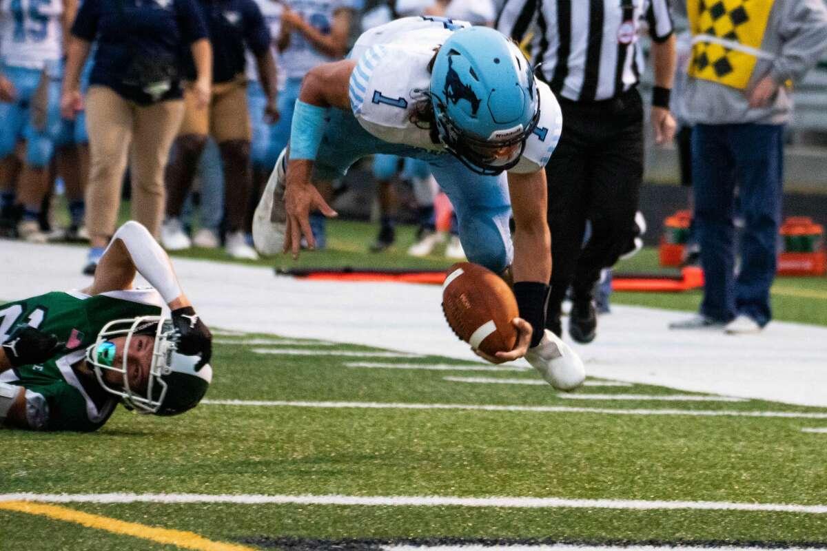 Quarterback junior Meridian Brayden Riley mematahkan tekel dan melayang ke udara menuju garis gawang selama pertandingan Jumat melawan Clare, 3 September 2021.