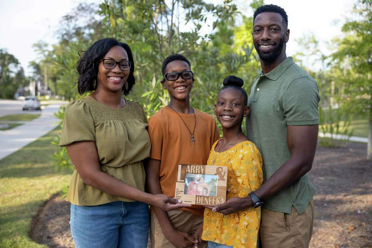 From left to right, Deneeka, Evan, 14, Addisyn, 10 and Larry Hunter pose for a portrait as they hold a family portrait that was salvaged from a house fire, at Founders Park at The Woodlands Hills subdivision, Wednesday, Sept. 1, 2021, in Conroe. Their home in Conroe's The Woodlands Hills subdivision was destroyed after an Aug. 11 house fire caused by lightning.