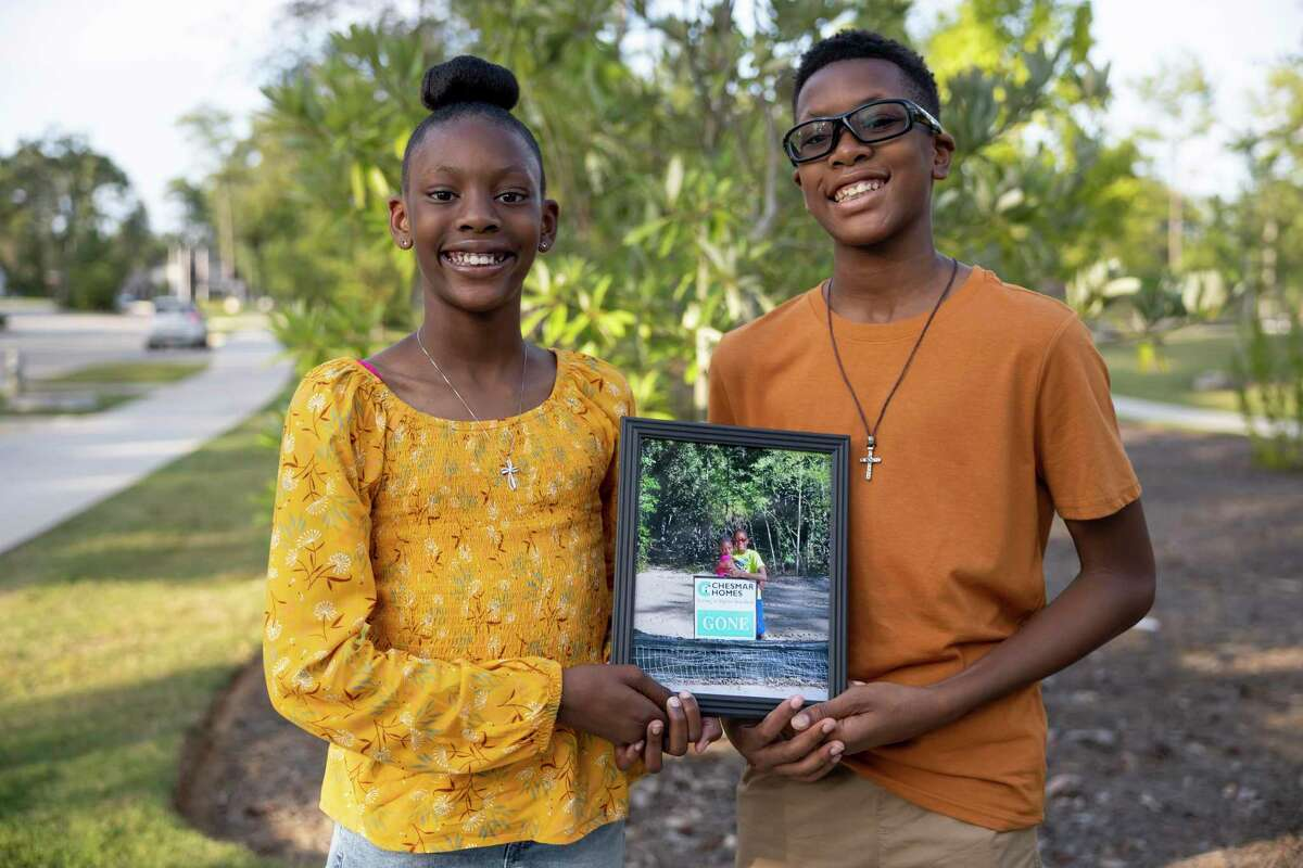 Addisyn Hunter, 10, left and Evan, pose for a portrait with an image of the two at the location of where their home would be built, at Founders Park at The Woodlands Hills subdivision, Wednesday, Sept. 1, 2021, in Conroe. Their home in Conroe's The Woodlands Hills subdivision was destroyed after an Aug. 11 house fire caused by lightning.