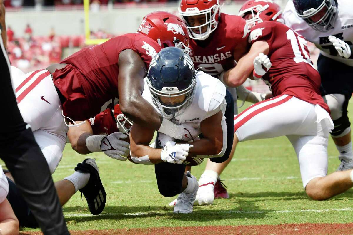 Rice running back Jordan Myers (7) breaks through the Arkansas defense to score a touchdown during the first half of an NCAA college football game, Saturday, Sept. 4, 2021, in Fayetteville, Ark. (AP Photo/Michael Woods)