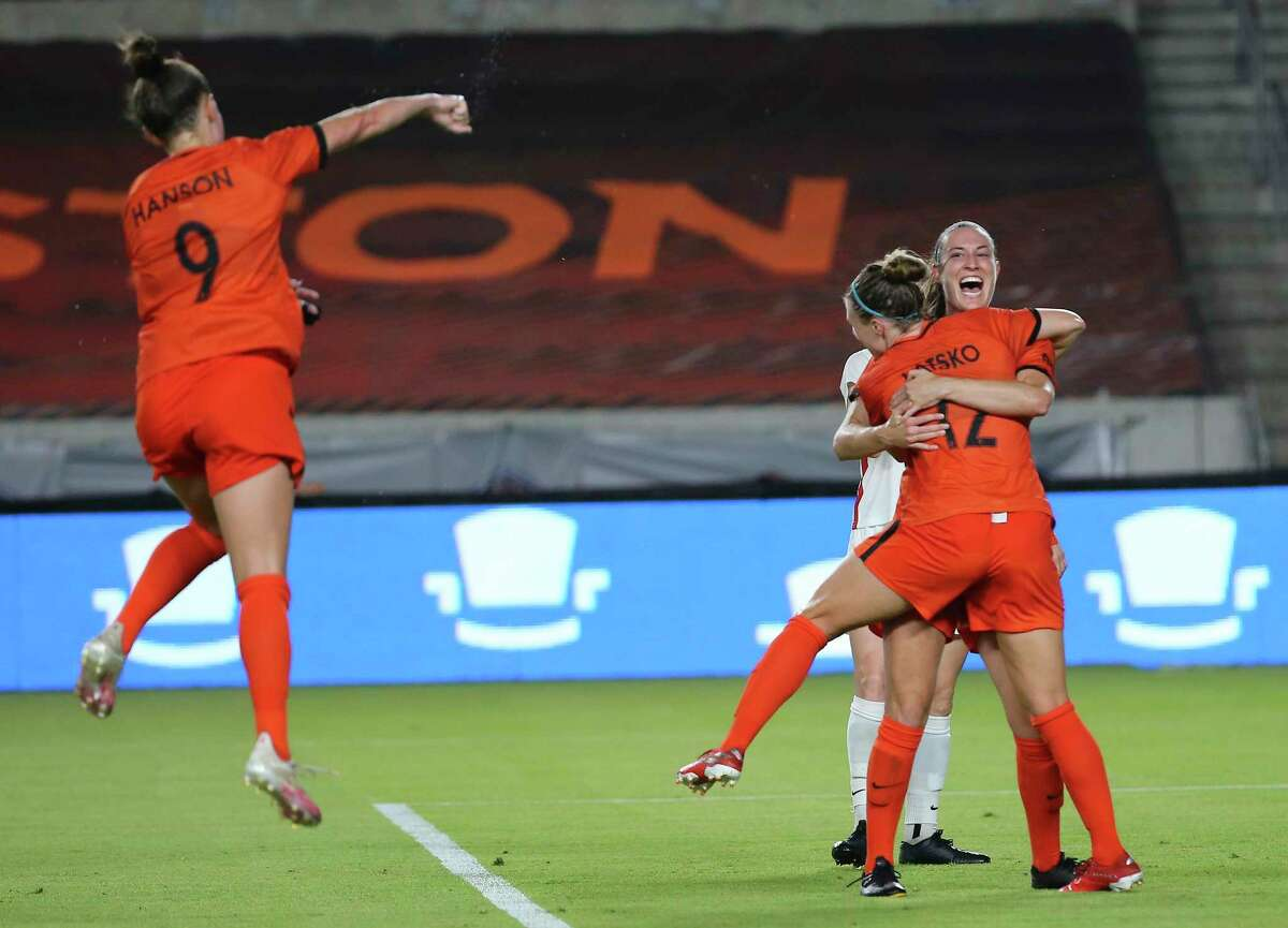Houston Dash defender Katie Naughton (25), forward Veronica Latsko (12) and defender Haley Hanson (9) celebrate Naughton's goal during the second half of the NWSL match against the OL Reign Friday, July 2, 2021, at BBVA Stadium in Houston.