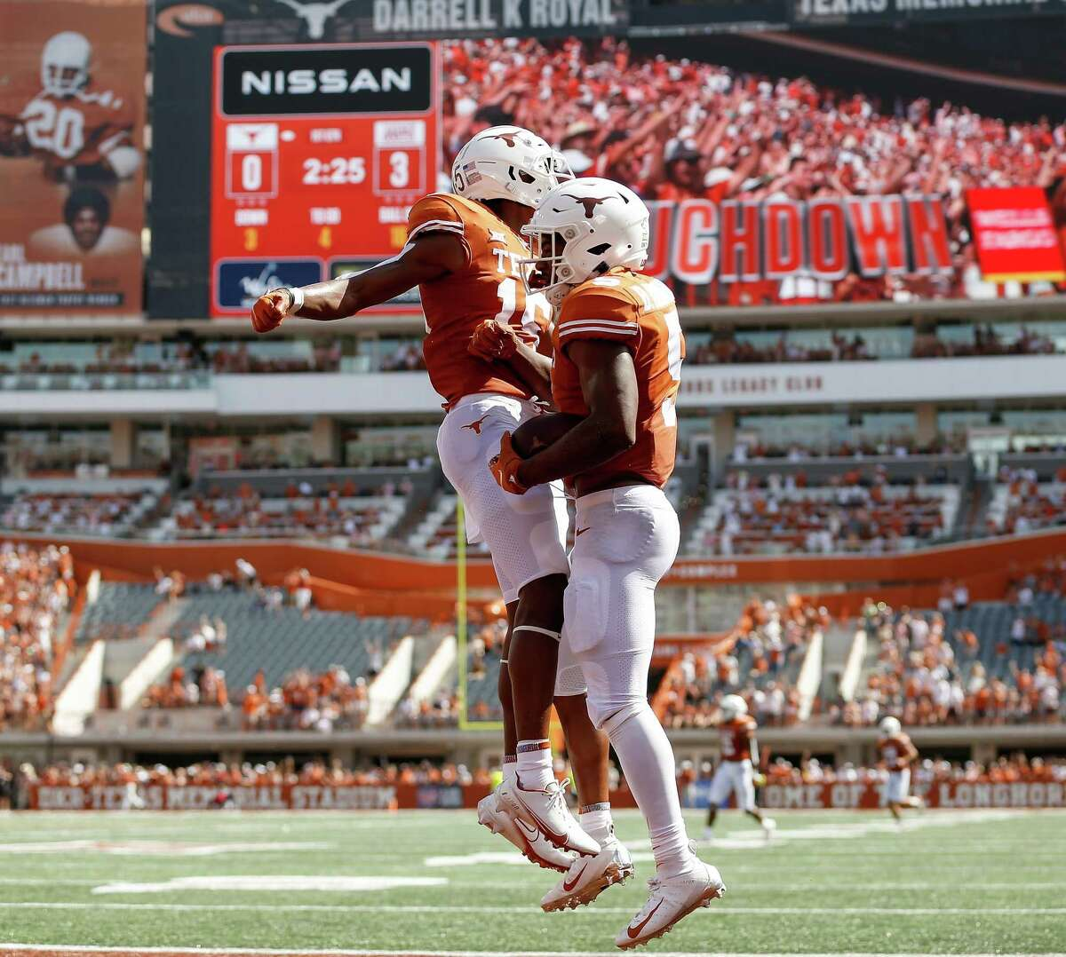 AUSTIN, TEXAS - SEPTEMBER 04: Marcus Washington #15 of the Texas Longhorns celebrates with Bijan Robinson #5 after a touchdown in the first quarter against the Louisiana Ragin' Cajuns at Darrell K Royal-Texas Memorial Stadium on September 04, 2021 in Austin, Texas.