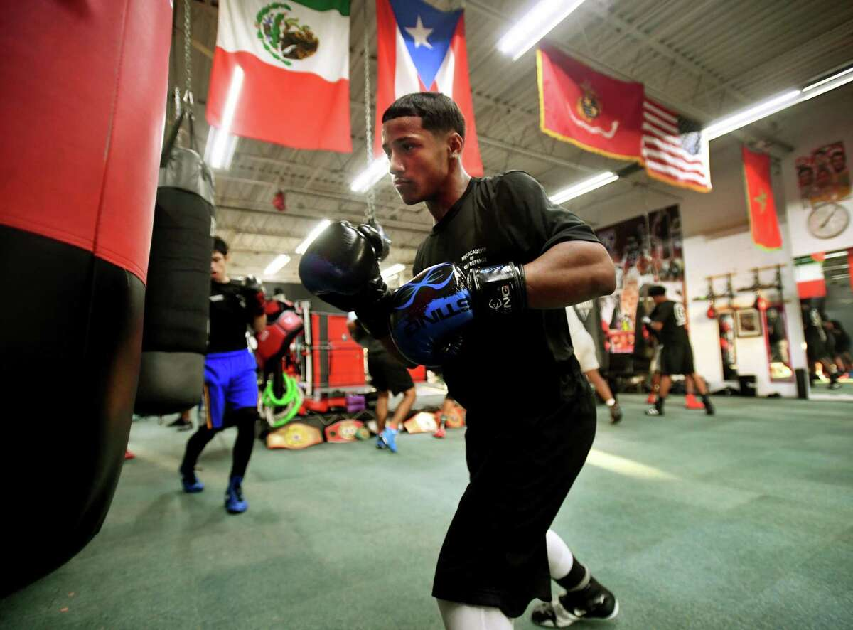 Joseph Chisholm, 15, of Stratford, hits the heavy bag along with his fellow boxers at the Chick Rosnick Boxing Club in Stratford, Conn. on Monday, August 16, 2021.