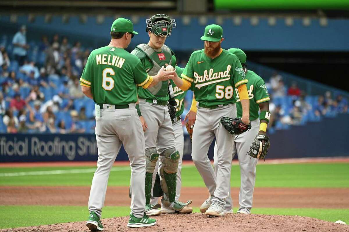 Oakland Athletics' manager Bob Melvin (6) pulls pitcher Paul Blackburn (58) in the fourth inning of a baseball game against the Toronto Blue Jays in Toronto on Saturday, Sept. 4, 2021. (Jon Blacker/The Canadian Press via AP)