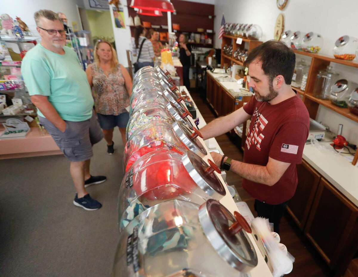 Reed Watson bags candy for a customer at The Candy House, Saturday, Sept. 4, 2021, in The Woodlands. Watson is part of a five-person ownership group who recently purchased the local business from long-time owner Don Baker who died in January 2021 after being hospitalized with COIVD-19.