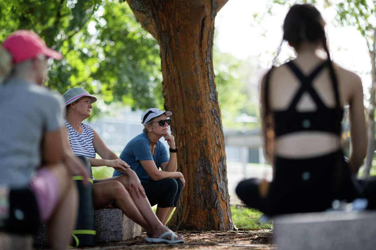 A group of people learn about mindfulness and meditation as part of Grounding with the Trees at Buffalo Bayou Park, Saturday, Sept. 4, 2021, in Houston. The practice is inspired by Forest Bathing movements in South Korea and Japan. The lesson was led by Heather Sullivan, a mindfulness instructor.