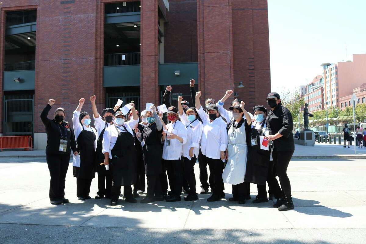 This photograph, provided by UNITE HERE Local 2, shows concession workers at the San Francisco Giants ballpark raising their fists near Oracle Park on the same day 96.7% of food service workers voted in favor to strike in response to concerns over safety during the coronavirus pandemic, health care and hazard pay.