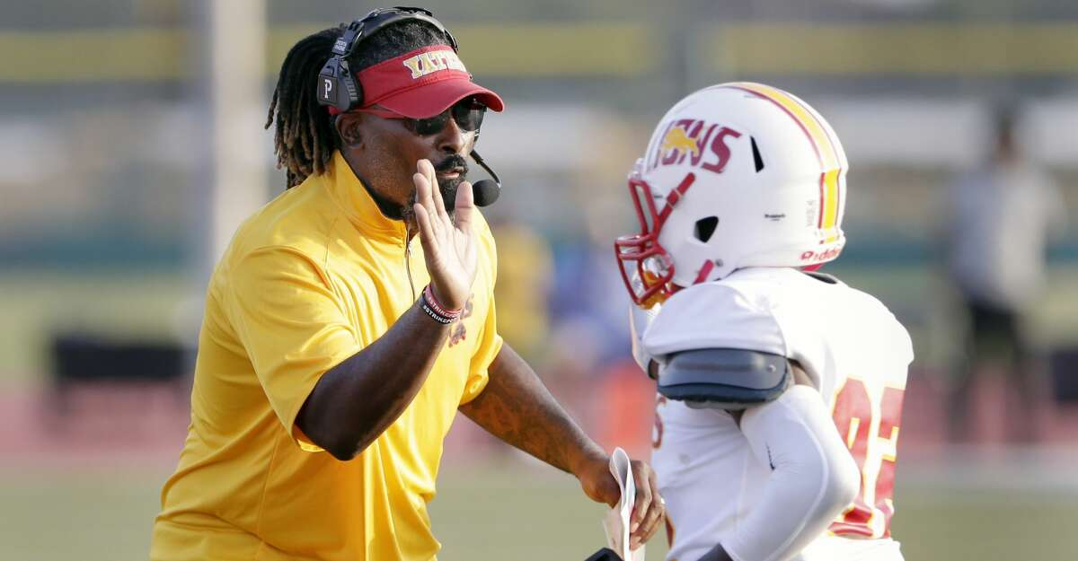 Yates head coach Troy DeGar high fives Gerald McAfee after a touchdown against Madison during the first half of a high school football game at Butler Stadium Saturday, Sept. 4, 2021 in Houston, TX.