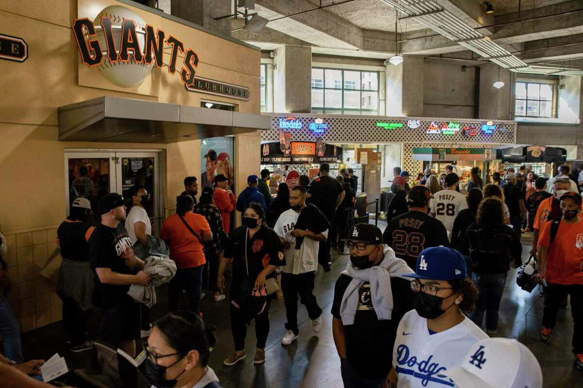 Fans visit vendors as Unite Here Local 2, a union representing about 930 concessions workers at Oracle Park held a strike vote shortly before a baseball game between the San Francisco Giants and the Los Angeles Dodgers in San Francisco, Saturday, Sept. 4, 2021. (AP Photo/John Hefti)