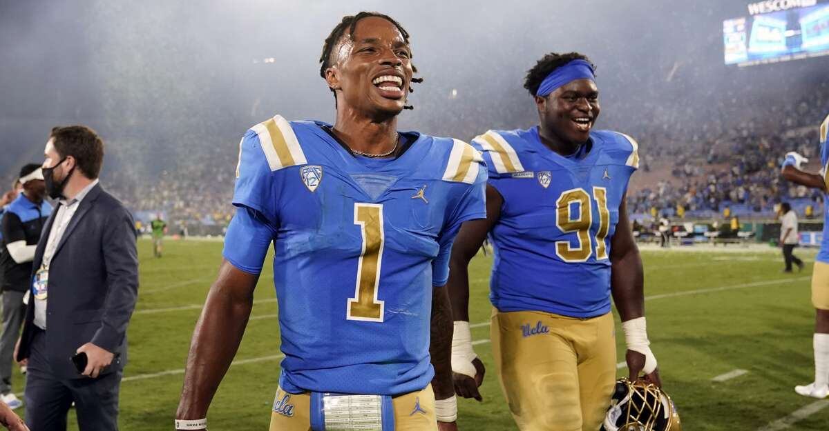 UCLA quarterback Dorian Thompson-Robinson (1) and defensive lineman Otito Ogbonnia (91) walk off the field after the team's win over LSU in an NCAA college football game Saturday, Sept. 4, 2021, in Pasadena, Calif. (AP Photo/Marcio Jose Sanchez)