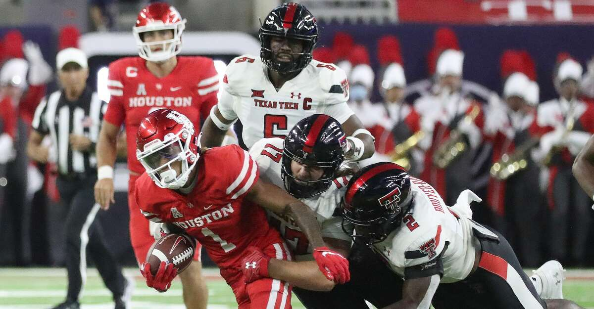 Houston Cougars wide receiver Nathaniel Dell (1) is brought down by Texas Tech Red Raiders linebacker Colin Schooler (17) and Brandon Bouyer-Randle (2) during the second quarter of the Texas Kickoff college football game at NRG Stadium, Saturday, September 4, 2021, in Houston.