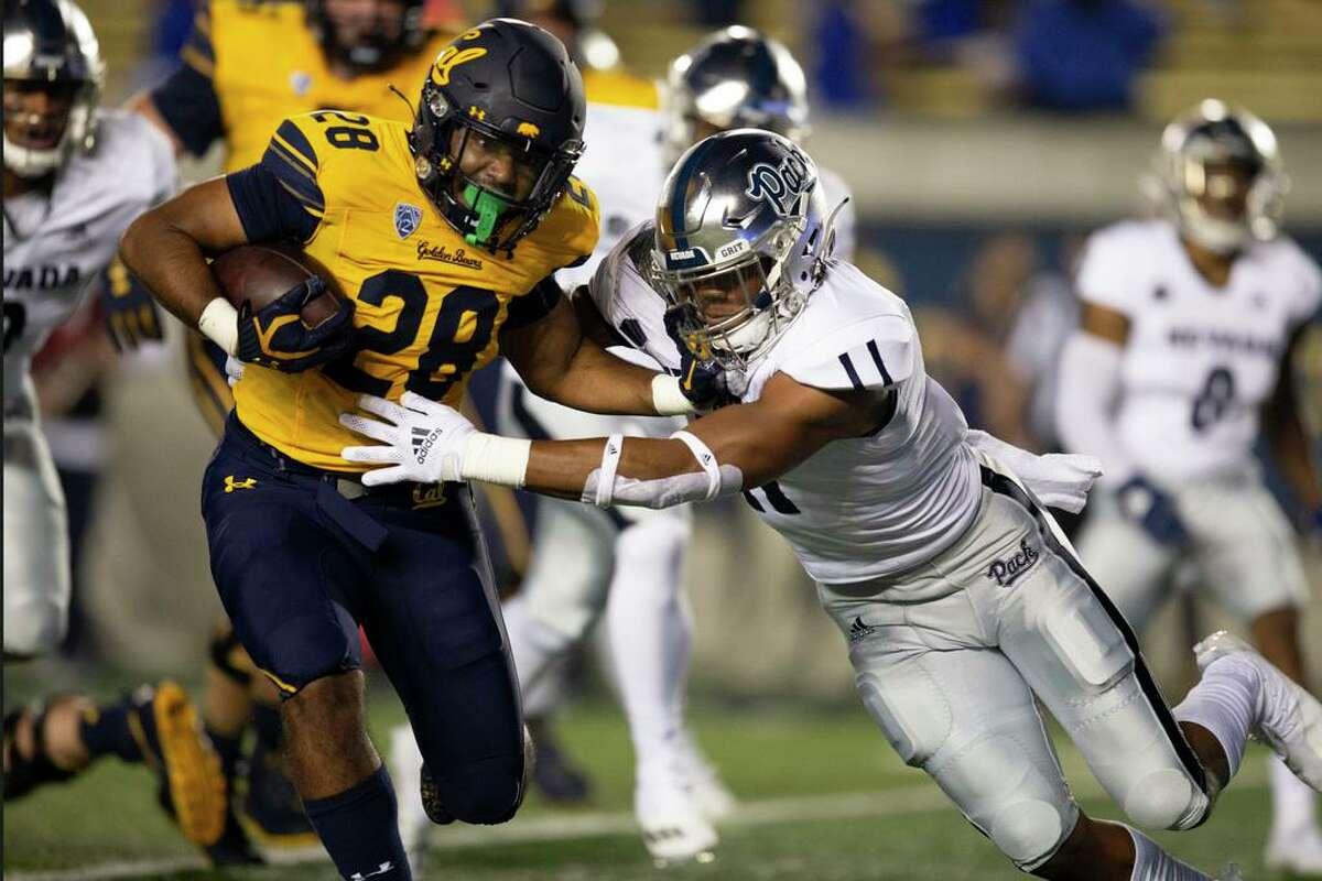 California running back Damien Moore (28) fends off Nevada linebacker Daiyan Henley (11) during the first quarter of an NCAA college football game Saturday, Sept. 4, 2021, in Berkeley, Calif. (AP Photo/D. Ross Cameron)