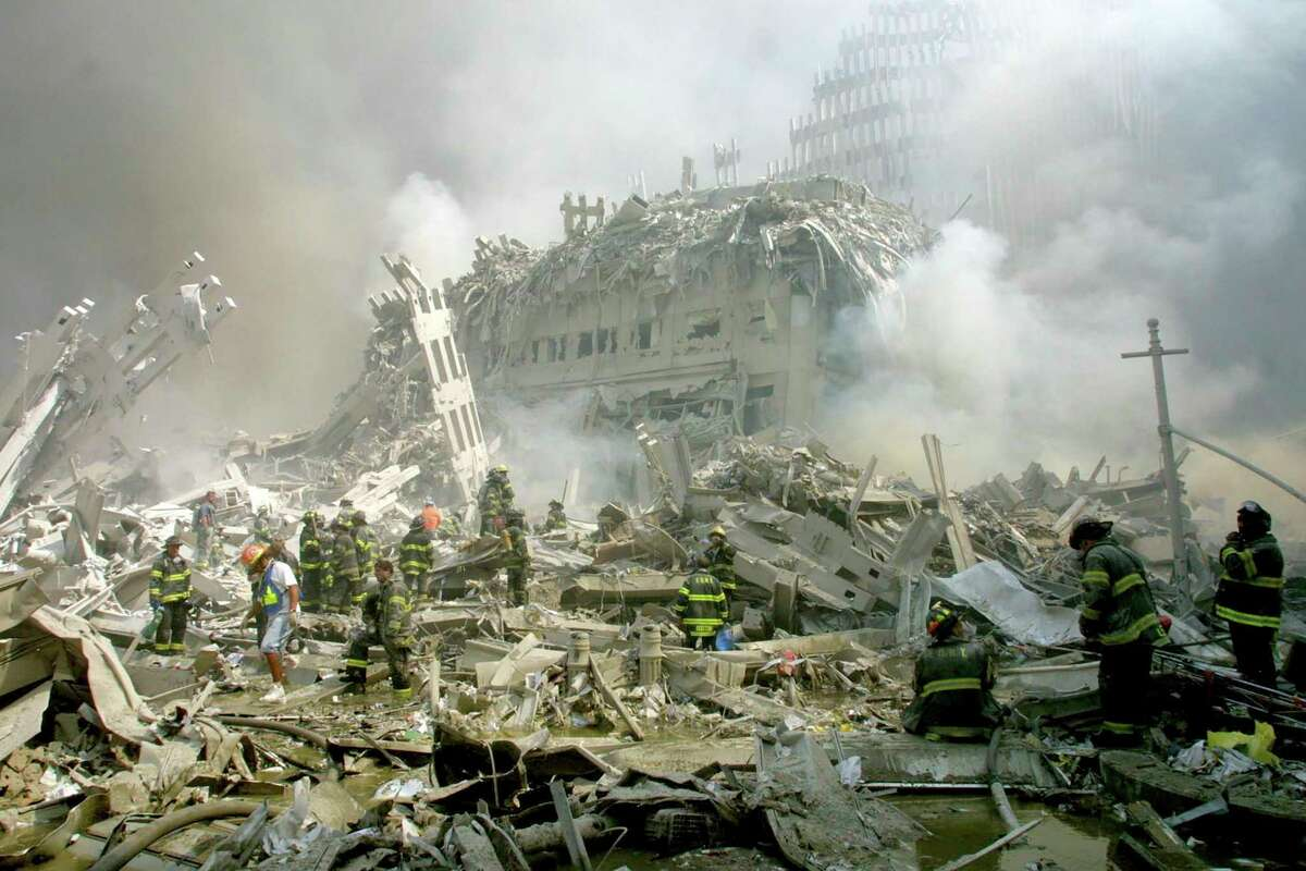 Firefighters make their way through the rubble after terrorists crashed two airliners into the World Trade Center in a deadly series of blows that brought down the twin 110-story towers in New York Tuesday, Sept. 11, 2001.