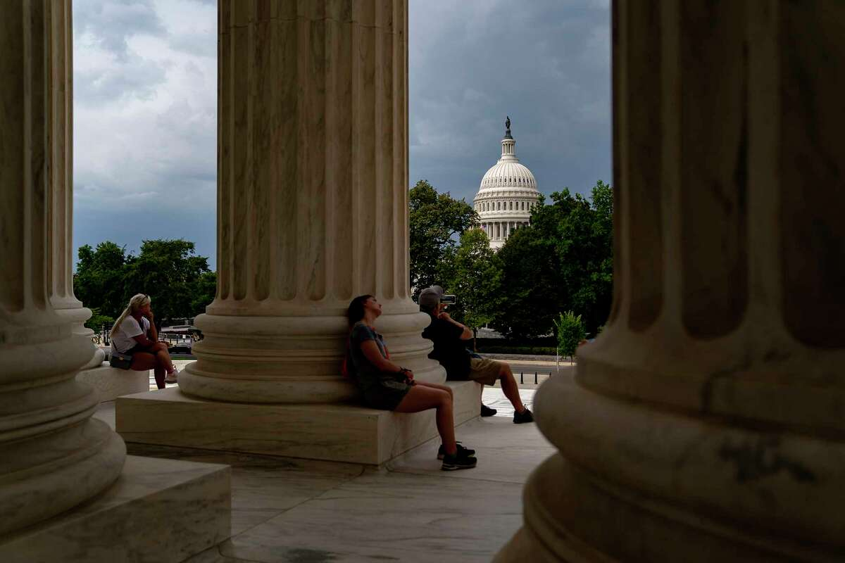 The U.S. Capitol is seen as visitors wait out a storm at the Supreme Court in Washington, D.C., on Aug. 13.
