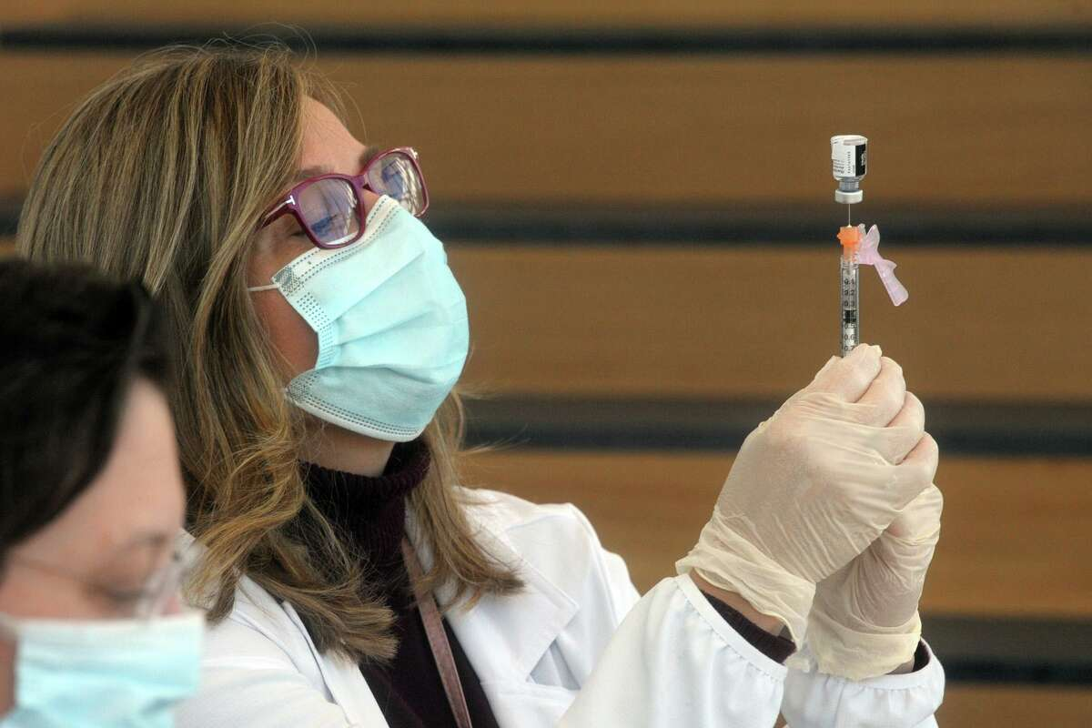 Gina Christakos fills a syringe with COVID-19 vaccine at Hartford HealthCare's new mass vaccination clinic on the west campus of Sacred Heart University, in Fairfield.