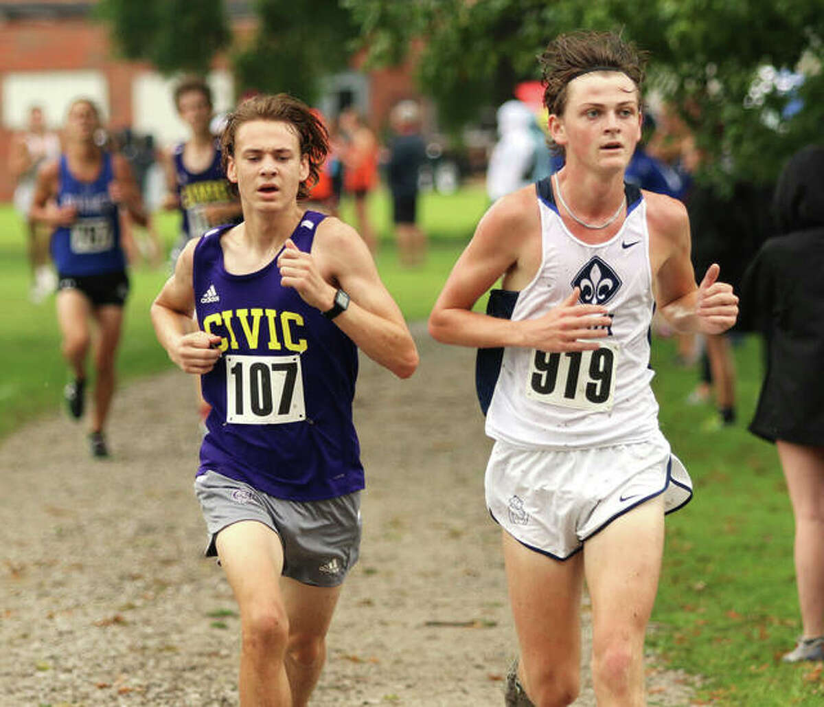 CM's Jackson Collman runs alongside SLUH's Joseph LaBarge (919) in the final 400 meters of the 3-mile cross country race at the Granite City Invite on Saturday morning at Wilson Park. Collman finished 18th, with LaBarge in 20th in a field of 201 boys.
