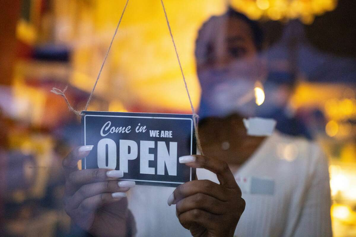 Woman turning an open sign on glass front door of coffee shop.