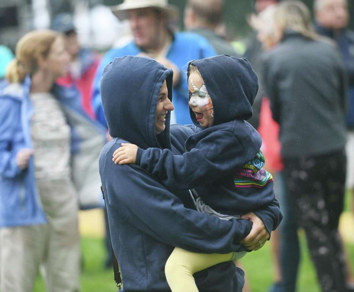 Whitney Chefnoff dances in the rain with Lily Cole, 4, as Greenwich country singer-songwriter Caroline Jones performs at the Greenwich Town Party at Roger Sherman Baldwin Park in Greenwich, Conn. Sunday, Sept. 5, 2021. This year's lineup featured headliners Zach Brown Band and the Eagles.