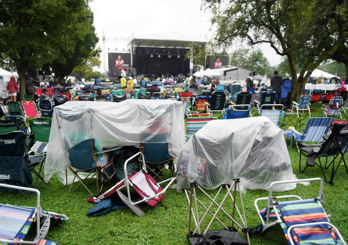 Folks shield themselves from the rain as Greenwich country singer-songwriter Caroline Jones performs at the Greenwich Town Party at Roger Sherman Baldwin Park in Greenwich, Conn. Sunday, Sept. 5, 2021. This year's lineup featured headliners Zach Brown Band and the Eagles.